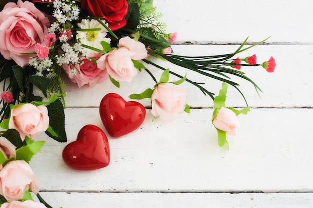 Walentynki romantyczne czerwone serce i bukiet kolorowych kwiatów na białym drewnianym stole