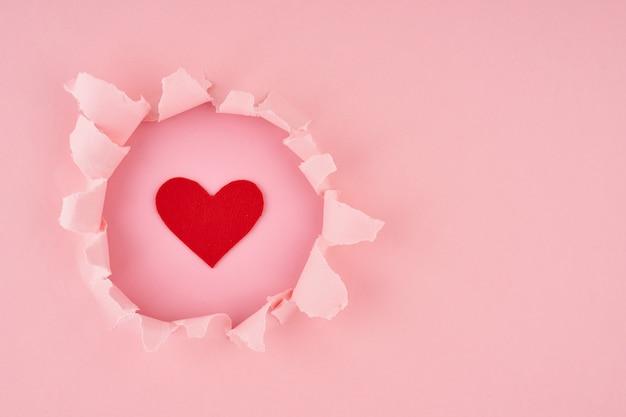 Walentynki. rozerwana dziura i czerwone serce w jasnoróżowej fakturze