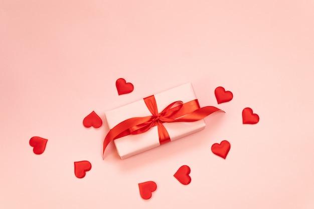 Walentynki. różowe pudełko z czerwoną kokardą, uwielbiam czerwony kształt na różowym tle. leżał płasko, widok z góry, miejsce.