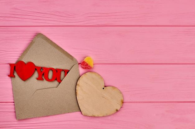 Walentynki różowe tło drewniane. koperta z drewnianą figurą kocham cię, serce ze sklejki i cukierki w kształcie serca, kopia przestrzeń.
