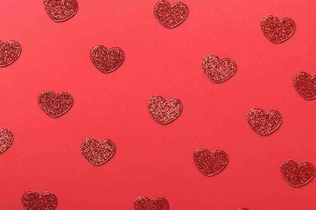 Walentynki ściany z czerwonym brokatem serca na czerwonej ścianie, widok z góry.