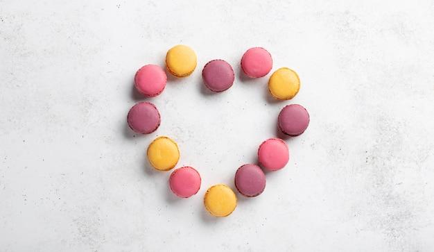 Walentynki serce wykonane z macarons w różnych kolorach. dzień kobiet. białe tło betonowe, baner