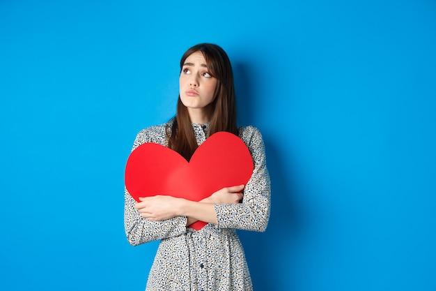 Walentynki smutna dziewczyna ze złamanym sercem szlocha patrząc w bok na pustą przestrzeń i płacze zdenerwowana przytulając bi...