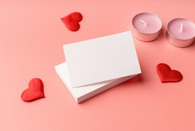 Walentynki. stos wizytówek na różowym tle z sercami i świecami do makiety projektu