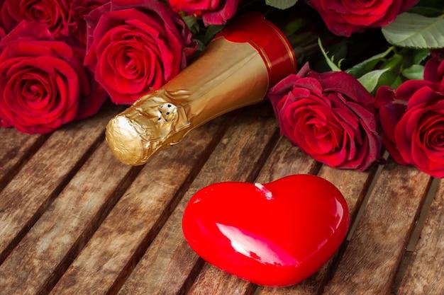 Walentynki szampańskie wino z czerwonymi różami i świecą