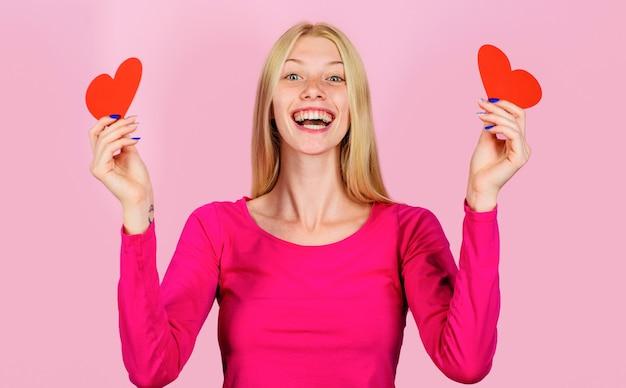 Walentynki, szczęśliwa dziewczyna na walentynki z sercem, uśmiechnięta kobieta z czerwonym sercem, koncepcja miłości.