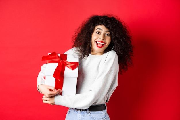 Walentynki. szczęśliwa dziewczyna trzyma pudełko od tajemniczego wielbiciela, patrząc romantycznie na kochanka, odbiera prezent, stojąc na czerwonej ścianie.