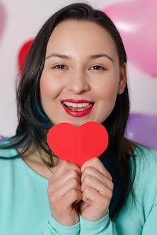 Walentynki. szczęśliwa kobieta trzyma w rękach pocztówkę w kształcie serca.