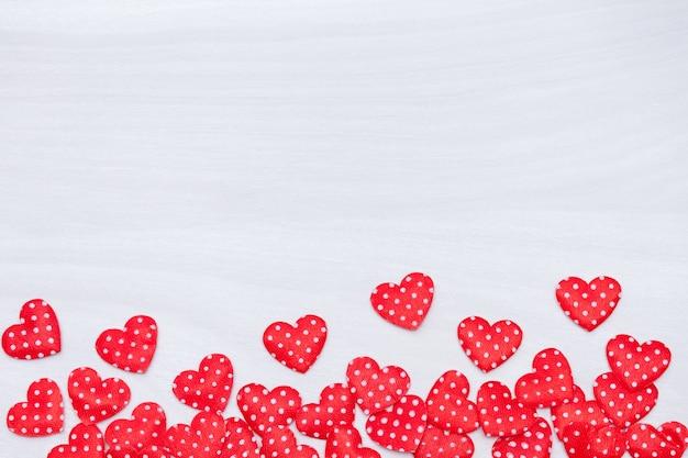 Walentynki tło. czerwoni serca na białym drewnianym tle. walentynki, miłość, koncepcja ślubu. leżał płasko, widok z góry.