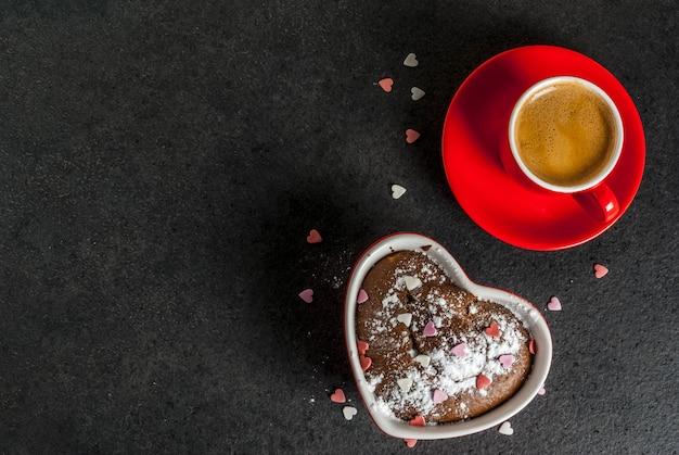 Walentynki tło, czerwony kubek kawy i ciasto czekoladowe kubek lub brownie z cukrem pudrem i posypką w kształcie serca, czarne tło, miejsce