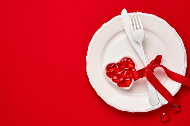 Walentynki tło lub koncepcja z pustym różowym talerzem i zastawą na szkarłatnym lub czerwonym tle. widok z góry płasko leżał z miejscem na kopię.