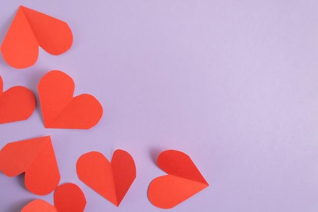 Walentynki tło. różowe i czerwone serca na pastelowym fioletowym tle.