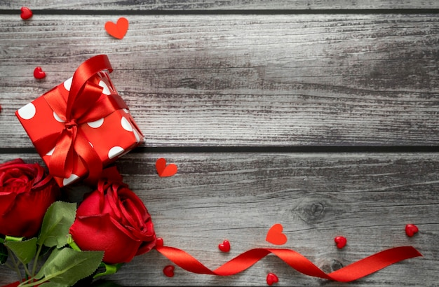 Walentynki tło. widok z góry na różę, pudełko, serca i wstążki na drewnianym stole z miejsce na tekst.