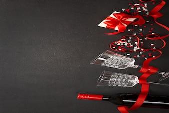 Walentynki tło. wino, serca, prezent, szklanki na ciemnym betonie