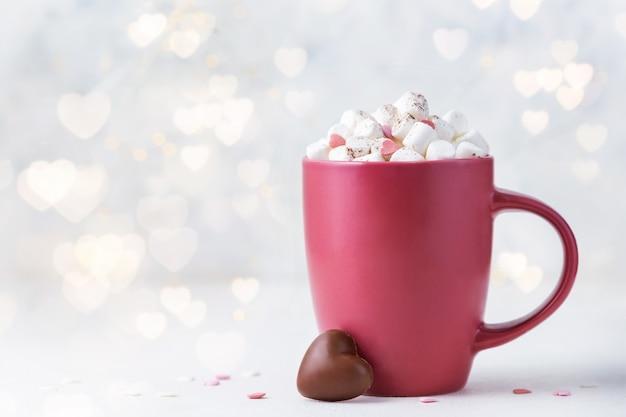 Walentynki tło z bokeh światłem. czerwony kubek z kakao, piankami i cukierkami czekoladowymi
