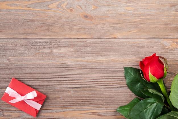 Walentynki tło z czerwoną różą i kopertą walentynkową na drewnianym stole, płaskie leżały z miejsca na kopię.