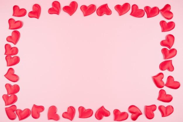 Walentynki tło z czerwonym sercem, na różowym tle, miejsce na tekst