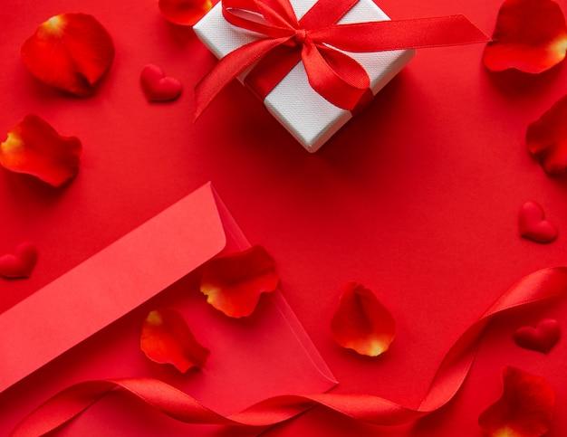 Walentynki tło z prezentem, kopertą i płatkami róży