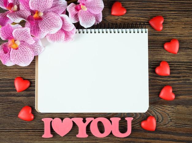 Walentynki tło z pustą notatką, słowo kocham cię, kwiat i czerwone serca na brązowej powierzchni drewnianej