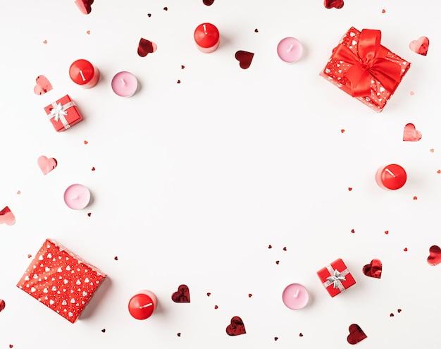 Walentynki tło ze świecami, prezentami, sercami i konfetti widok z góry mieszkanie leżało na białym tle. skopiuj miejsce