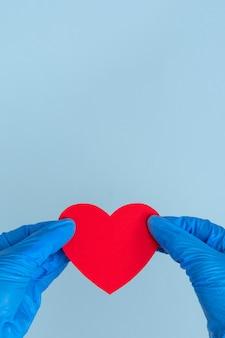 Walentynki w czasie pandemii koronawirusa. dwie niebieskie dłonie rękawiczki lateksowe trzymają kształt czerwonego serca na niebieskim tle, z bliska, kopia przestrzeń, ramka pionowa
