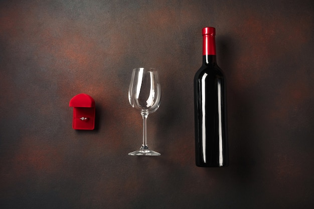 Walentynki z butelką wina i kieliszkiem oraz pierścionkiem zaręczynowym.