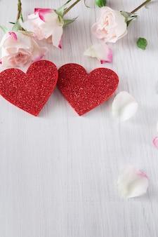 Walentynki z płatkami różowych kwiatów róży i ręcznie robionymi drewnianymi serduszkami z brokatem na białym rustykalnym drewnie