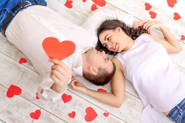 Walentynki, zakochana para leży wśród serc na podłodze, przytulając i trzymając duże czerwone serce