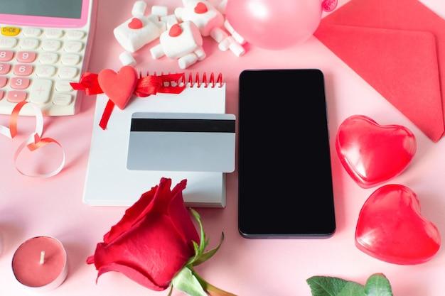 Walentynki zakupy online. sezonowa wyprzedaż świąteczna. karta kredytowa, smartfon, kalkulator, czerwona róża, czerwone serca.