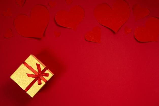 Walentynki złote pudełko z czerwoną wstążką i papierowym sercem na tle.