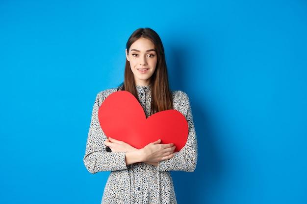 Walentynkowa atrakcyjna młoda kobieta szukająca miłości trzyma duże czerwone serce i uśmiecha się do...