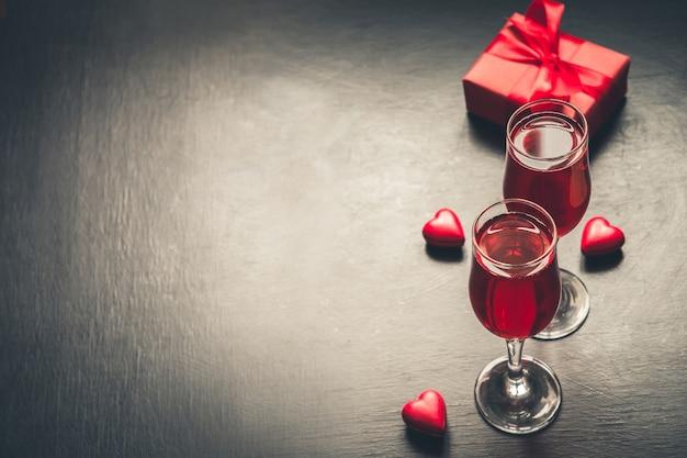 Walentynkowa karta z szampanem i kierowym cukierkiem na czerni.