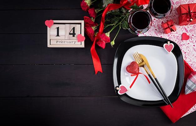 Walentynkowa kolacja z nakryciem stołu z prezentem, czerwone róże, serca z dwoma kieliszkami na ciemno