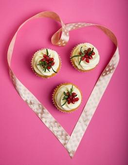 Walentynkowe babeczki z lukrem waniliowym i ozdobione wstążkowym sercem.
