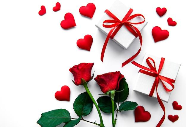 Walentynkowe pudełka i czerwone róże na białej powierzchni