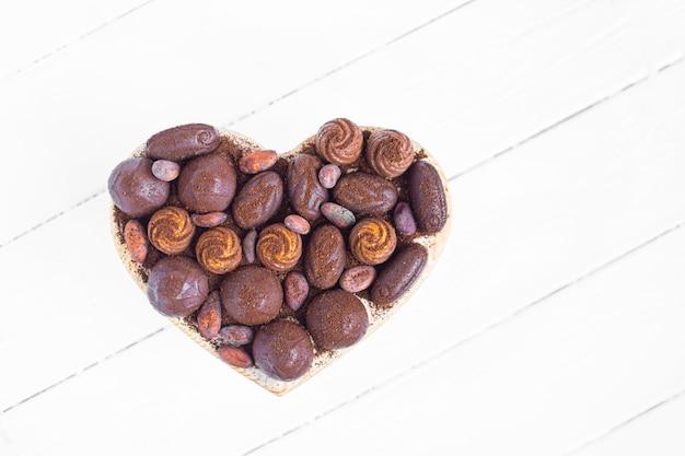 Walentynkowe pudełko w kształcie serca z czekoladkami, fasolką kokosową i kakao na białym drewnianym tle