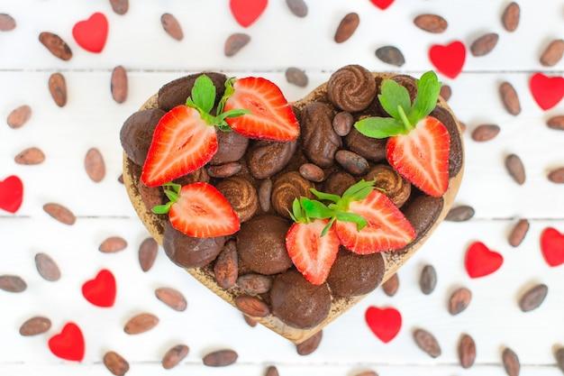 Walentynkowe pudełko w kształcie serca z czekoladkami i świeżymi truskawkami