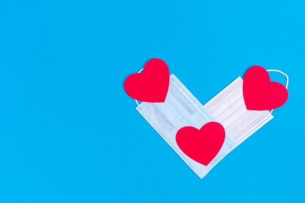 Walentynkowy symbol. w kształcie serca dwie medyczne maski ochronne i trzy czerwone serca