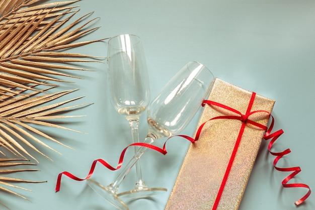 Walentynkowy układ kieliszków do szampana, liście palmowe ze srebrnym brokatem i pudełko z czerwonymi wstążkami na niebieskim tle