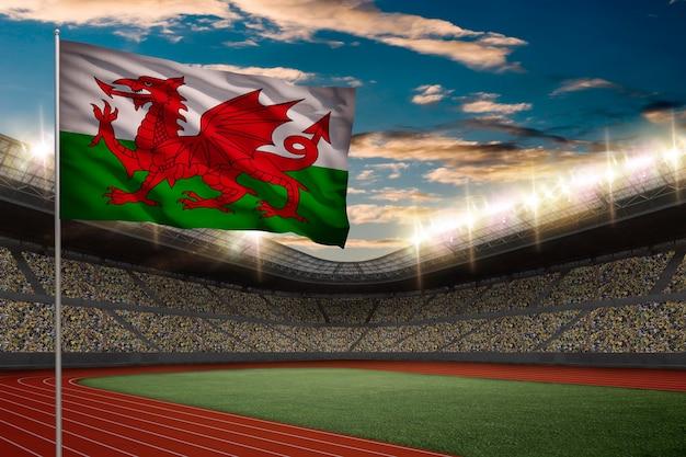Walijska flaga przed stadionem lekkoatletycznym z kibicami.