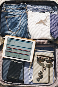 Walizka gotowa do podróży służbowej i bilet na ekran tabletu