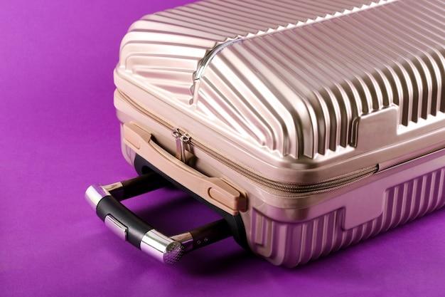 Walizka na fioletowym tle koncepcja podróży i wakacji