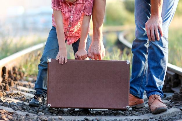 Walizka ojciec i syn trzymają walizkę w pobliżu linii kolejowej