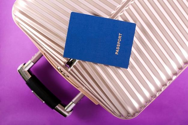 Walizka, paszport i kapelusz na fioletowym tle koncepcja podróży i wakacji