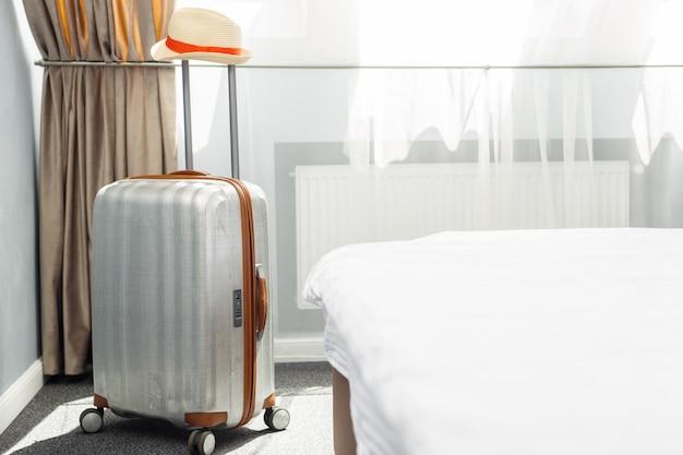 Walizka w jasnym pokoju hotelowym