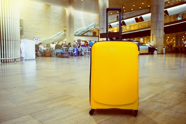Walizka w lotniskowym terminalu lotniska poczekalni z strefą wypoczynkową jako tło. koncepcja tematu wakacje.