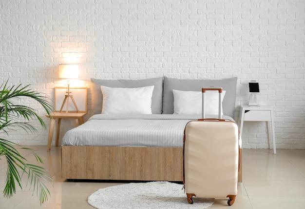 Walizka w nowoczesnym pokoju hotelowym