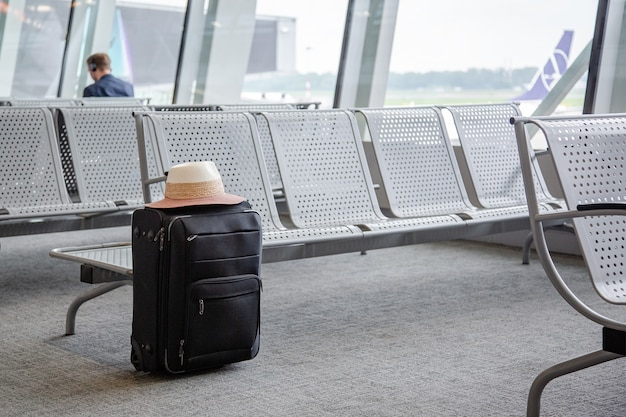 Walizka w poczekalni na lotnisku, jedna czarna walizka w poczekalni na lotnisku.
