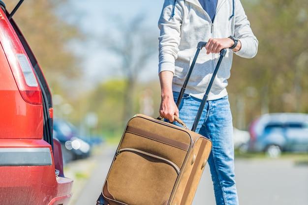 Walizka w ręku młody mężczyzna wyciągnął z bagażnika samochodu osobowego