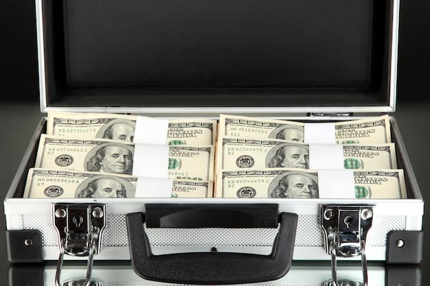 Walizka z 100 dolarowymi banknotami na czarno